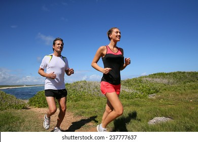 Couple running by the sea on track