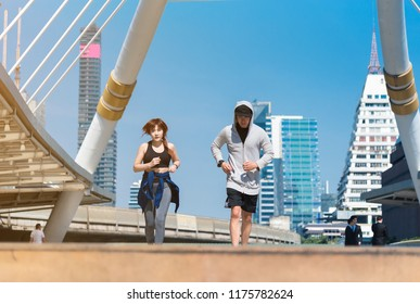 Couple running in the city at morning. Health conscious concept. Couple runners sprinting outdoors - Sportive people training in the city after finish work, sport and healthy lifestyle concepts