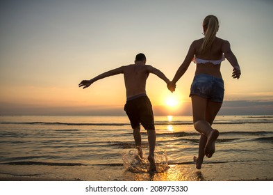 Couple running into water at sunrise