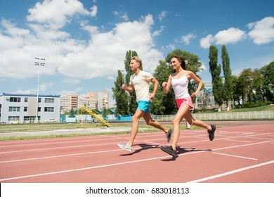 Couple running on arena track. Coach and trainer at workout. Runner on competition and future success. Man and woman sunny outdoor on blue sky. Sport and healthy fitness.