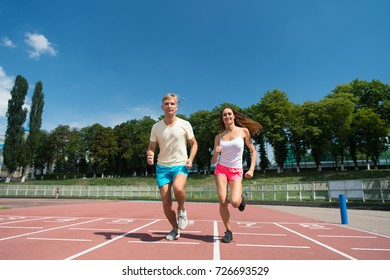Couple running on arena track. Sport and healthy fitness. Runner on competition and future success. Man and woman sunny outdoor on blue sky. Coach and trainer at workout.