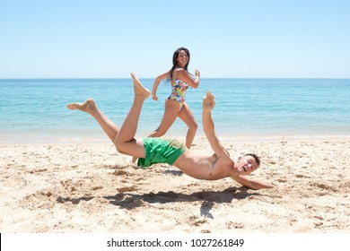 Couple running on the beach, boy falling on his face.