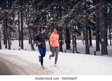 Couple running outdoors on a winter day.
