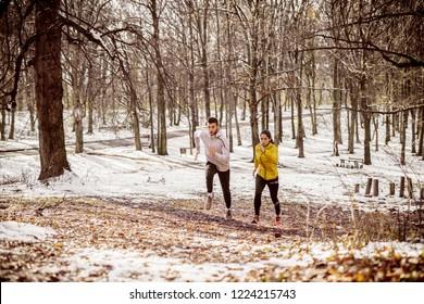 Couple running side by side in woods in winter.