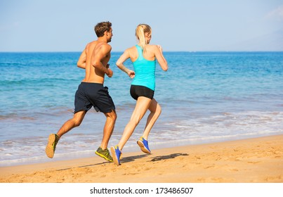 Couple running. Sport runners jogging on beach working out smiling happy. Fitness exercise concept.