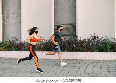 Couple running in an urban environment wearing protective masks