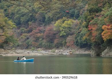 Couple sailing boat in river with autumn season at Arashiyama in Kyoto, Japan