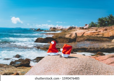 Couple of santa claus hat on tropical exotic paradise sandy beach with ocean waves and rocky coastline in background
