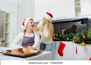 A couple in Santa Claus hats bake cupcakes on Christmas in the k
