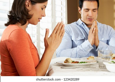 Couple Saying Grace Before Meal At Home