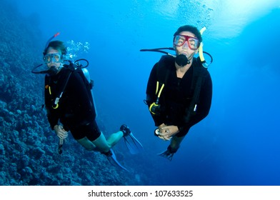 a couple scuba dive together in the ocean on a coral reef