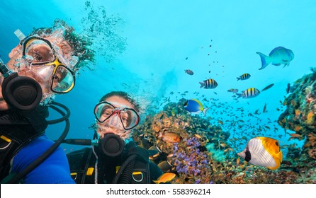 Couple of scuba divers looking at camera underwater. Beautiful coral reef with many fish on background