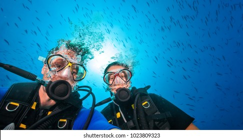 Couple of scuba divers, portrait photography. Underwater sports and activities