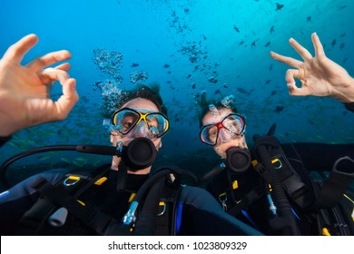 Couple of scuba divers showing ok sign, portrait photography. Underwater sports and activities