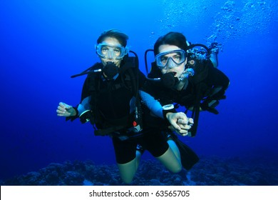 Couple Scuba Diving together in tropical ocean