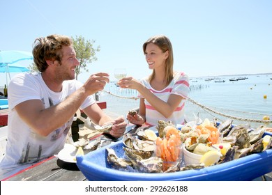Couple in seafood restaurant tasting fresh oysters