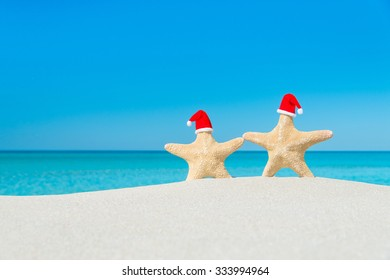 Couple of Sea-stars in red Santa hats walking at tropical beach. New Year's day or Christmas in hot countries vacation concept