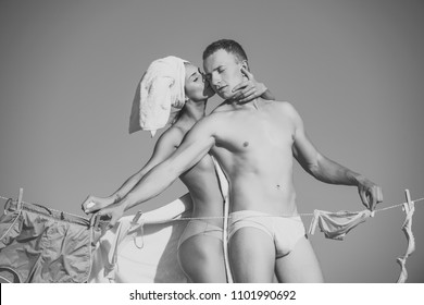 Couple secrets fantasy. sexy couple in love or family of woman in terry towel with muscular athletic man foreplay at clothesline rope with underwear on sunny blue sky background, household and summer