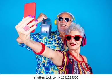 Paar Senior Mann und Frau auf blauem Hintergrund Selbstaufnahme - Opa und Oma live Streaming einzeln auf Stereo - Technologie, Clubbing, Spaß Konzept haben