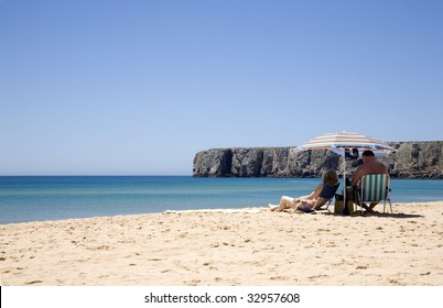 A couple of senior man and woman, sunbathing in a beach under a colourful umbrella at the Algarve, Portugal