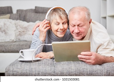 Couple of seniors listen to music with tablet on the couch