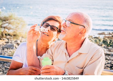 couple of seniors married sit on the beach blowing a bubble of soap with the sea in the background