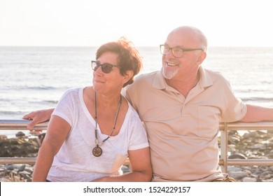 couple of seniors and mature people sitted on a bench at the beach with the sea at the background looking at the right together smiling and laughing