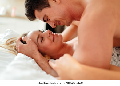Couple sensual foreplay in bed while lying on bed