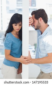 Couple are separated by white wall having relationship problems