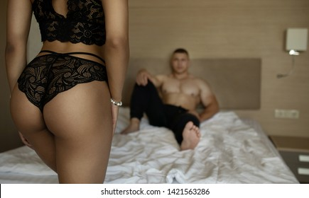 Couple. Sex. Back view of sexy woman in black panties, man is lying on the bed in the background.