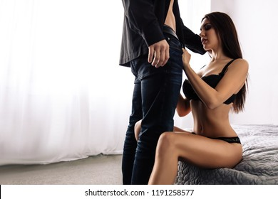 Couple. Sex. Passion. Young woman in black lingerie is unbuttoning man's jeans while sitting on bed