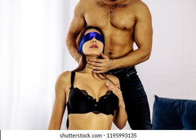 Couple. Sex. Role play. Sexy young woman with a blue bandage on her eyes, guy is touching her neck
