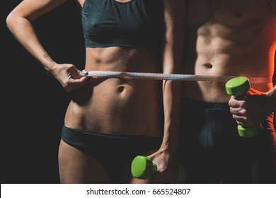 couple of sexy woman and athletic man with muscular body and torso hold dumbbell or barbell in hands and tape measure, sport and fitness, coach, workout, dieting and health