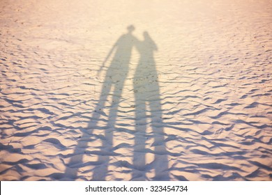 couple shadow  on the beach, sunset lighting, summer vacation concept unusual, selective focus, stylized