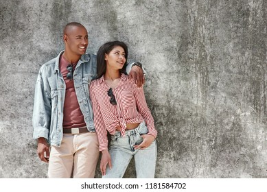 Couple shoot. Young diverse couple standing on the city street on wall hugging looking aside smiling relaxed
