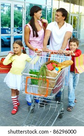 Couple with shopping bags and their two children pushing cart