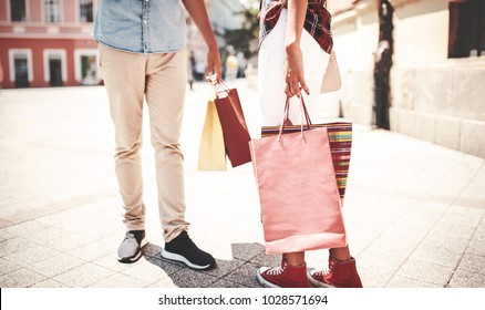 Couple in shopping. Close up photo of woman and man legs with shopping bags while walking down the street after shopping. Consumerism, fashion, lifestyle concept