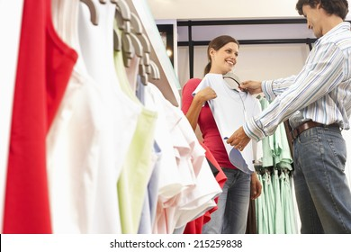 Couple shopping in clothes shop, man holding pale blue top up against girlfriend, smiling, side view
