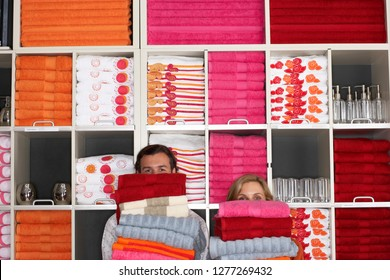 Couple shopping for homeware carrying stack of towels in shop obscuring their faces standing in front of colorful goods arranged on shelves