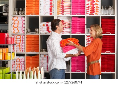 Couple shopping for homeware choosing towels in store in front of colorful goods arranged on shelves