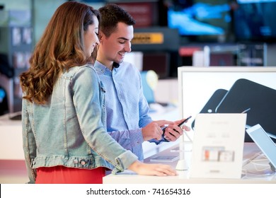 Couple shopping for latest laptop and smartphone at tech store