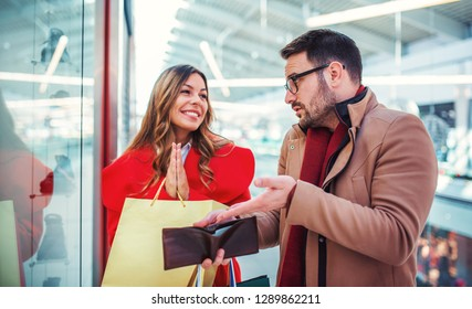 Couple in shopping mall. Man showing an empty wallet to his girlfriend. Consumerism, love, dating, lifestyle concept