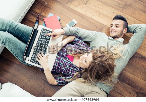 ノートパソコンでオンラインショッピングを2人で – リビングルームのノートパソコンでビデオを見ている若い友人が2人、上から見る