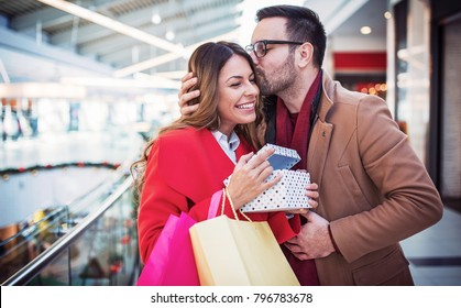 Couple in shopping. Young man surprised his girlfriend with a present for Valentine's day. Relationships, love, dating