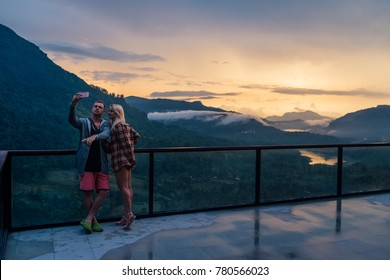 the couple should be photographed on the terrace on the background of a beautiful sunset in the mountains