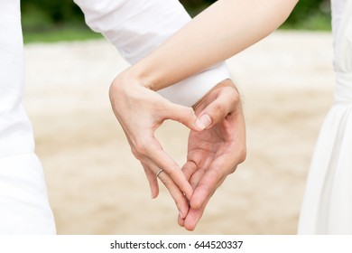 Couple showing their connection and feelings by holding their hands strongly in shape of heart; select focus.