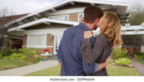 Couple shown from behind embracing and being affectionate outside new home