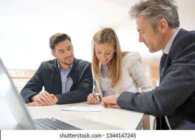 Couple signing contract with real estate agent
