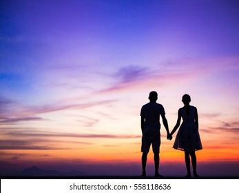 Couple silhouette holding hands watching a sunset