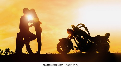 Couple silhouette kissing at sunset and have a big bike parked on the street.